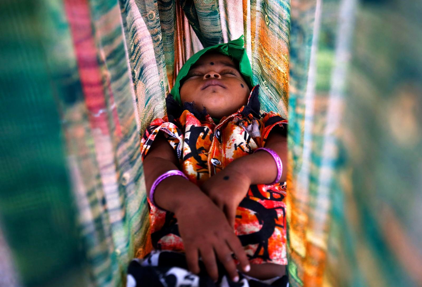 Barnet til en bygningsarbeider sover i en hammock utenfor byggeplassen i Bangalore i India.