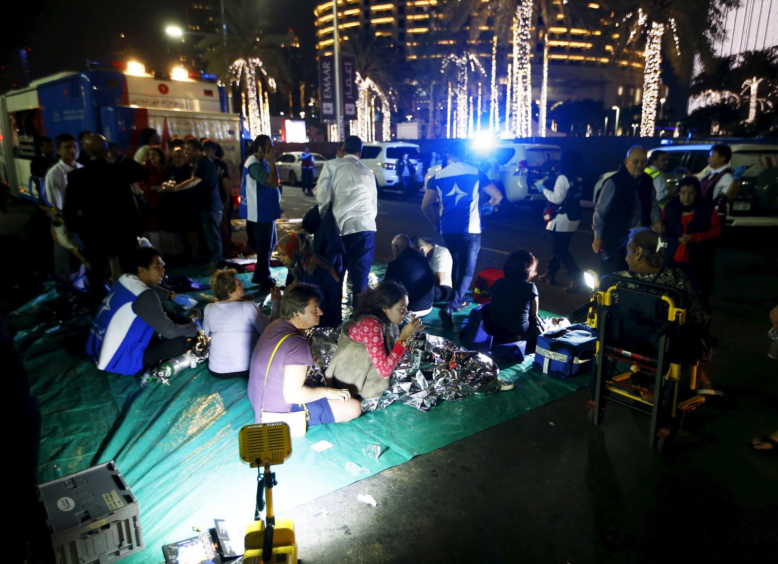 Skadde og evakuerte hotellgjester samlet utenfor Address Hotel i Dubai nyttårsaften.