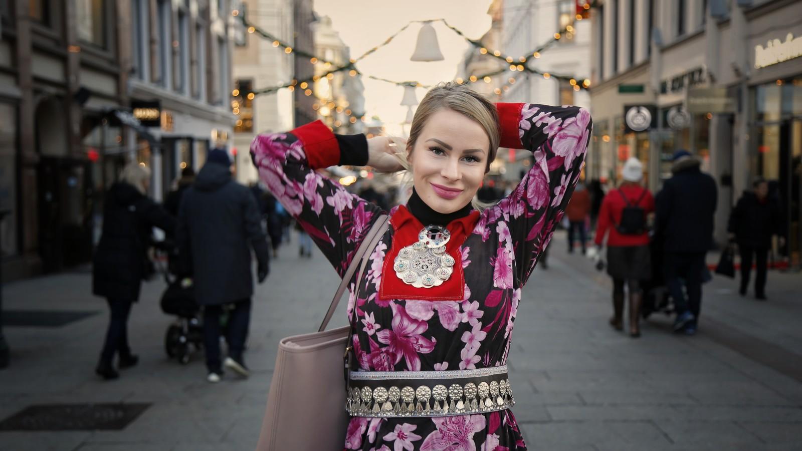 Halvnært bilde av en ung kvinne i samedrakt midt på Karl Johans gate i Oslo. Kvinnen smiler og løfter hendene opp bak nakken for å holde håret på plass. Kvinnen smiler. Hun har en blomstrete kofte på seg, sølvbete og to søljer og en gammelrosa Michael Kors veske over skulderen.