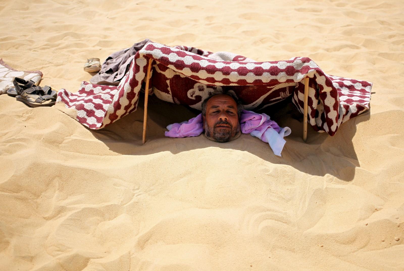 En manns hode stikker opp av den varme, egyptiske sanden i Siwa. Midt på dagen, da solen varmer som mest, lar folk seg grave ned i håp om at det skal hjelpe mot plager som revmatisme, impotens m.m.