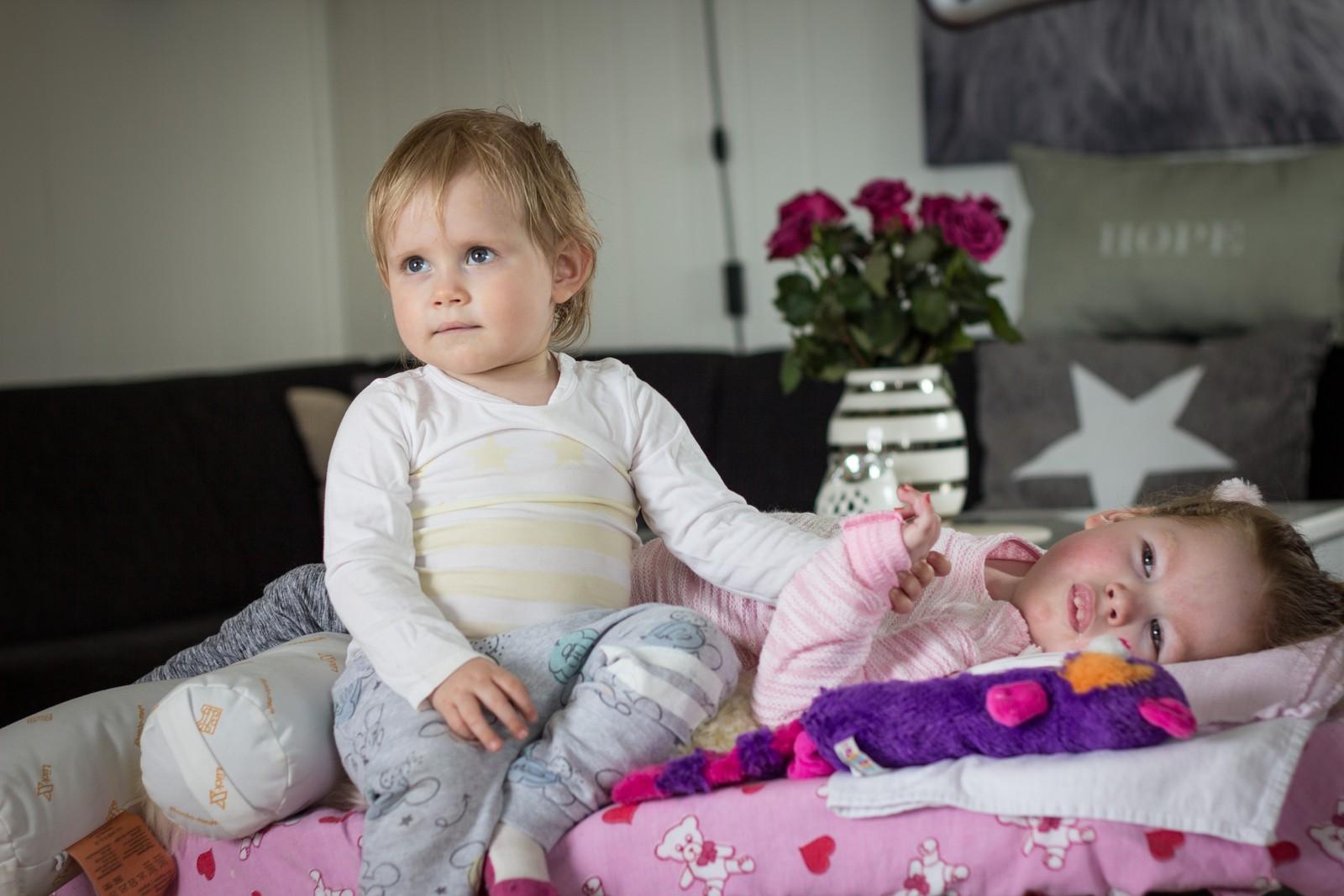 Amalie sitter på sengekanten og holder i hånda til Frida Amalie. De småler og ser på TV.