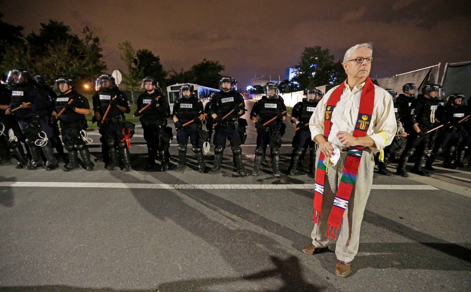 Charlotte Police Fatal Shooting A member of the clergy stands in front of a line of police officers in Charlotte, N.C. Thursday, Sept. 22, 2016. blocking the access road to I-277 on the third night of protests following Tuesday's fatal police shooting of Keith Lamont Scott. (AP Photo/Chuck Burton)