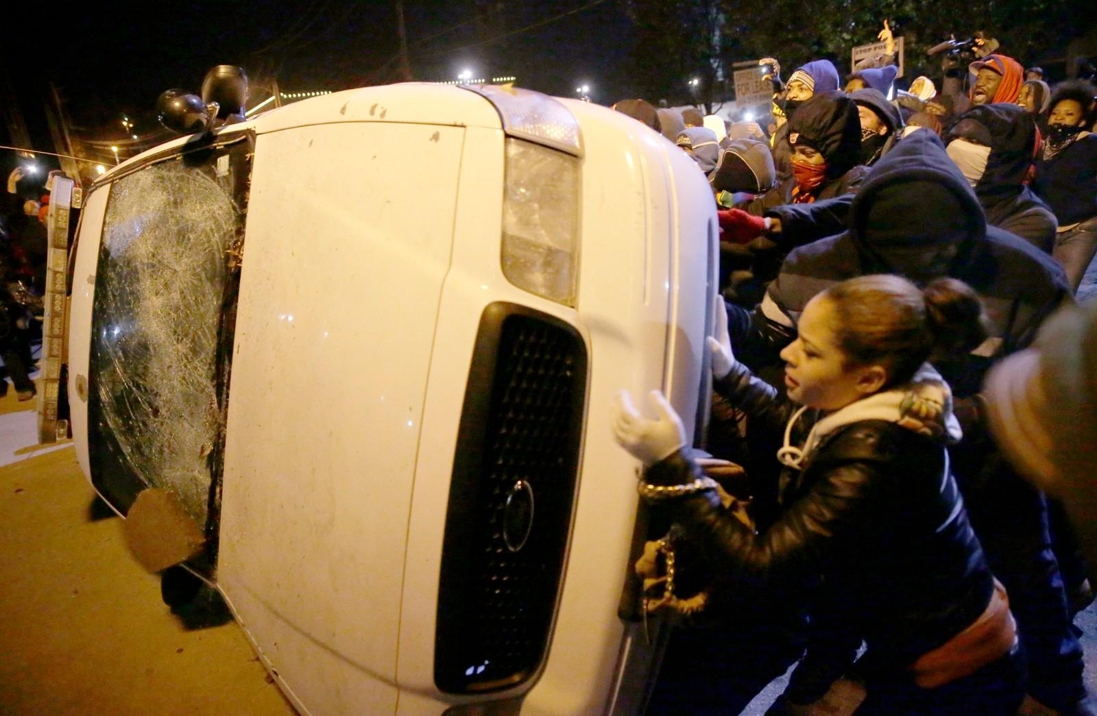 Demonstranter velter en politibil i Ferguson natt til onsdag.