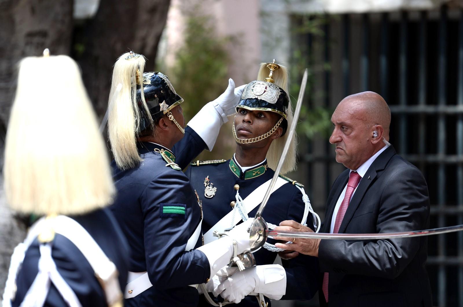 En æresvakt føler seg svimmel på grunn av varmen, og får hjelp under et besøk av den franske presidenten Francois Hollande i Lisboa i Portugal den 19. juli.