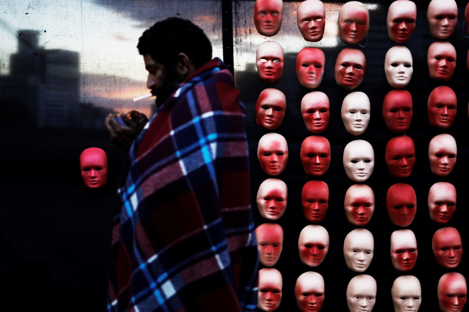 En hjemløs mann passerer en vegg med masker som skal forestille brasilianske politikere. Slike masker kan sees mange steder i landet i forbindelse med demonstrasjoner mot korrupsjon.