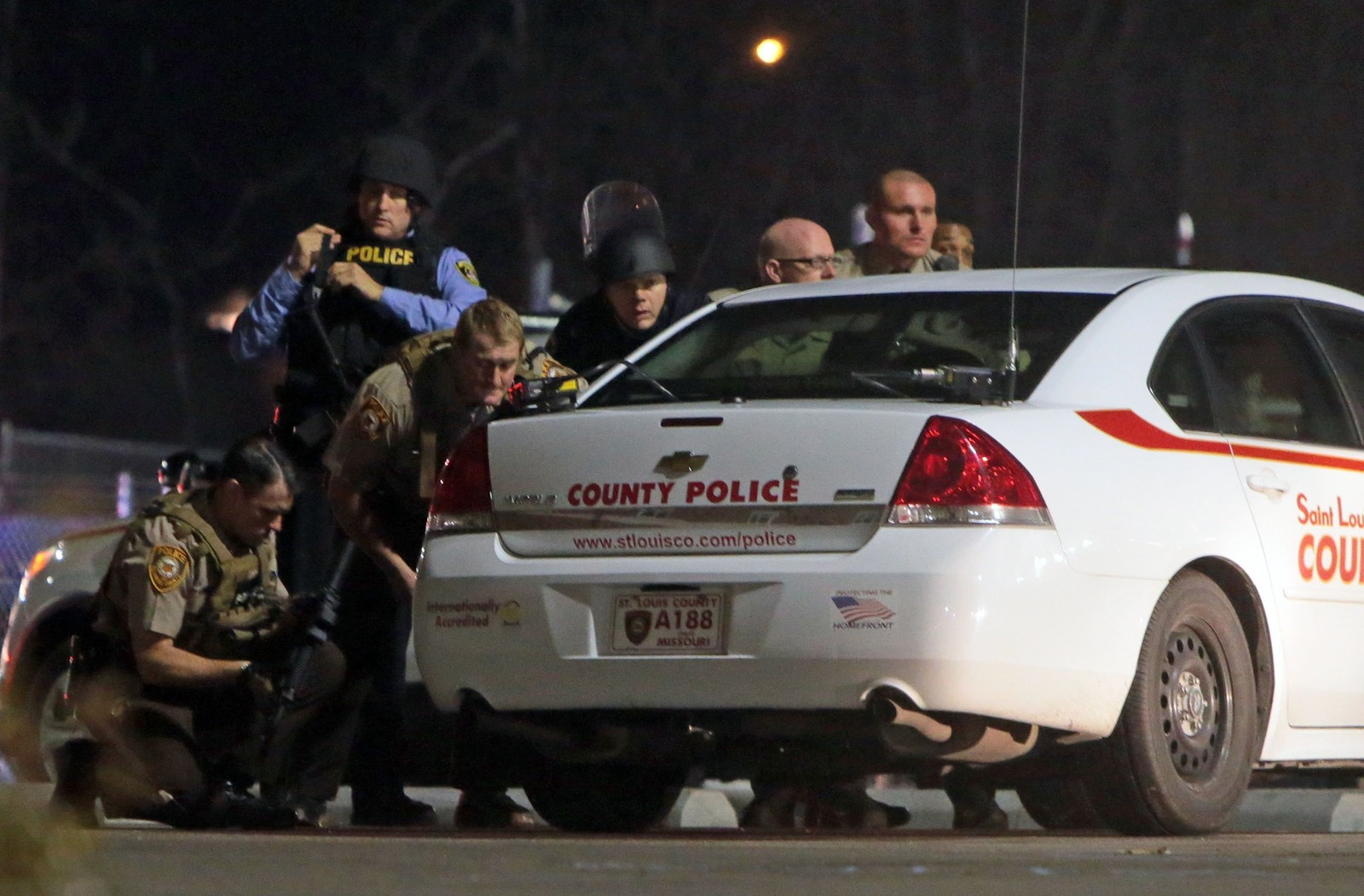 Politiet tar dekning bak en bil på parkeringsplassen utenfor politistasjonen i Ferguson etter politidrapene. (AP Photo/St. Louis Post-Dispatch, Laurie Skrivan)