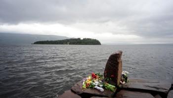 Blomster på brygga ved Utvika Camping for ofrene etter massakren på Utøya (i bakgrunnen)