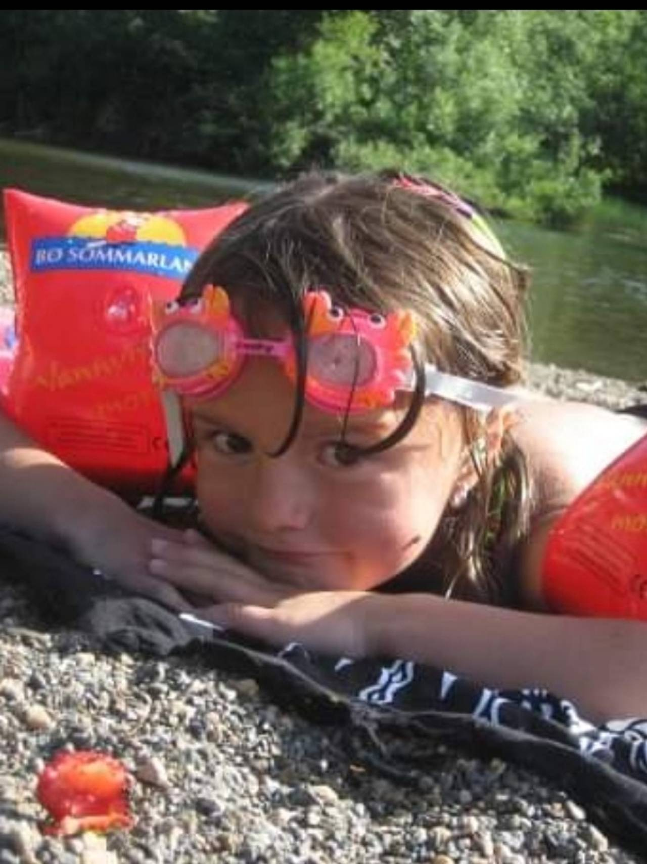 Andrine ligger på stranden med baderinger og svømmebriller.