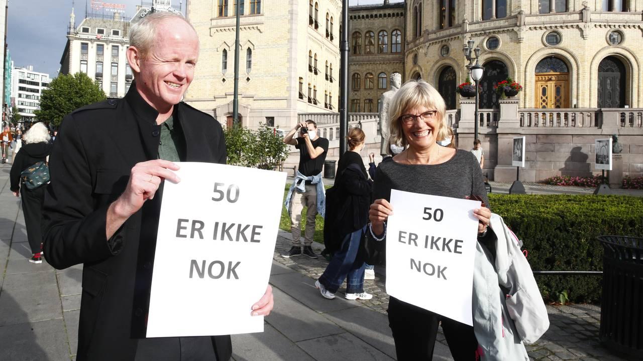 SV-politikerne Lars Haltbrekken og Karin Andersen utenfor Stortinget med plakater for å vise sin støtte til flyktningen i Moria-leiren