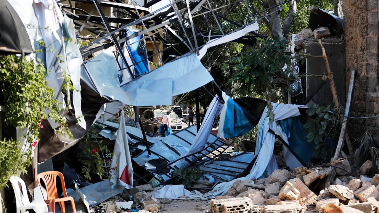 En kvinne bærer torsdag sine eiendeler ut av sitt ødelagte hus i Beirut.