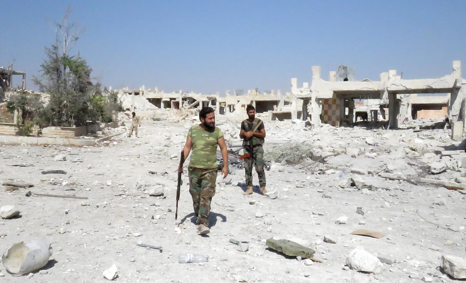 Syriske regjeringssoldatar i den tidlegare palestinske flyktningleiren Handarat i det nordlege Aleppo.