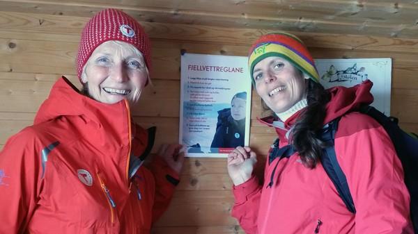 Astrid Kalstveit i DNT og Marit Aakre Tennø heng opp fjellvettreglane på nynorsk - Foto: Knut Webjørnsen
