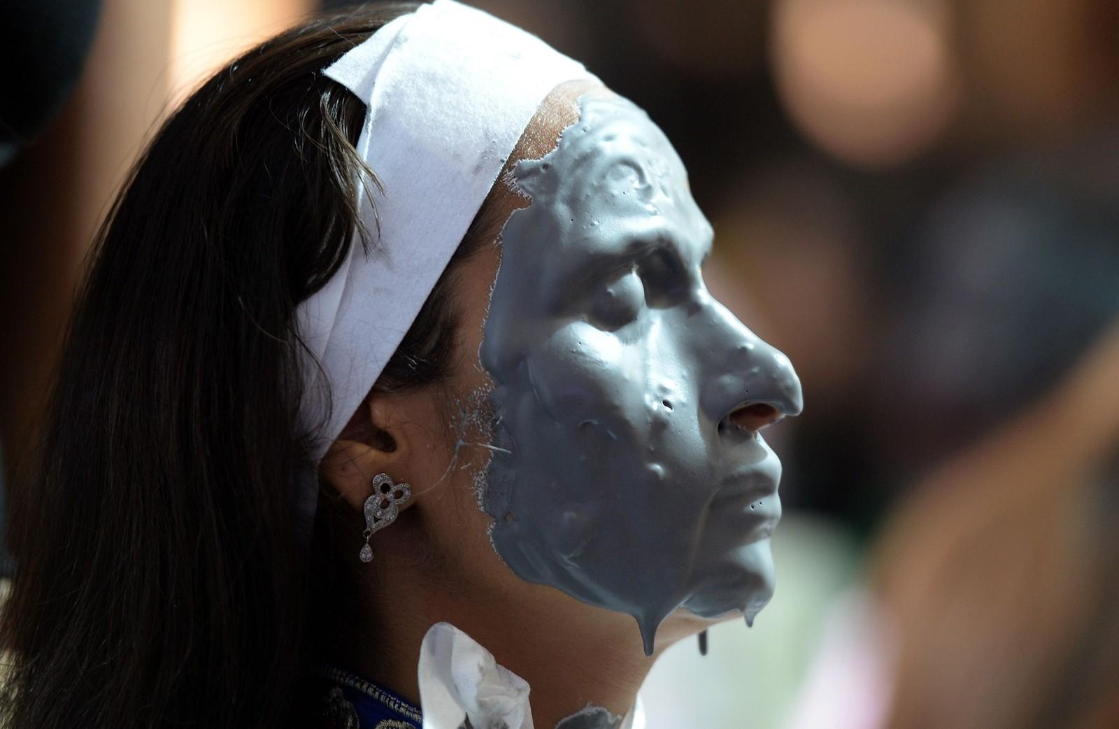 En indisk kvinne tester ut en ansiktsmaske basert på aske under en stor skjønnhetsmesse i New Dehli.