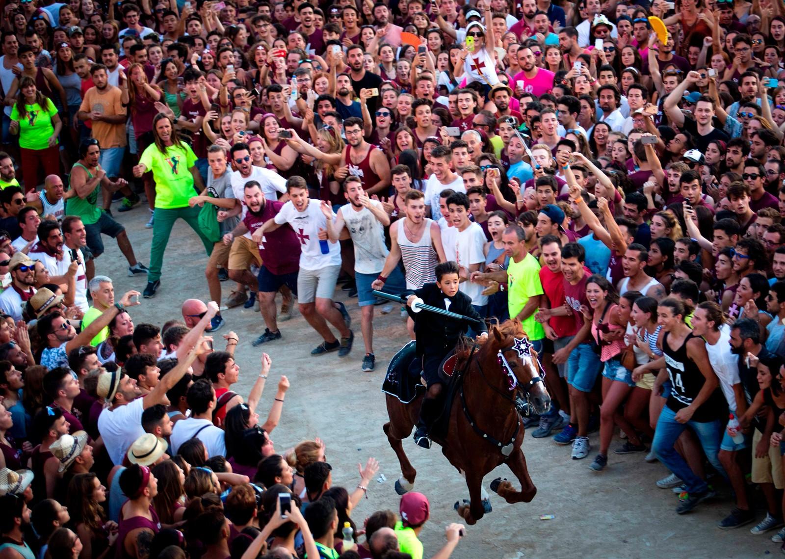 En gutt med lanse jubles for under San Juan-festivalen i byen Ciutadella på den spanske øya Menorca. Hester er viktige i feiringen av helgenen Johannes. Det er også den eksplosive drikken pomada, som er en blanding av den lokale ginen Mahon og lemonade.