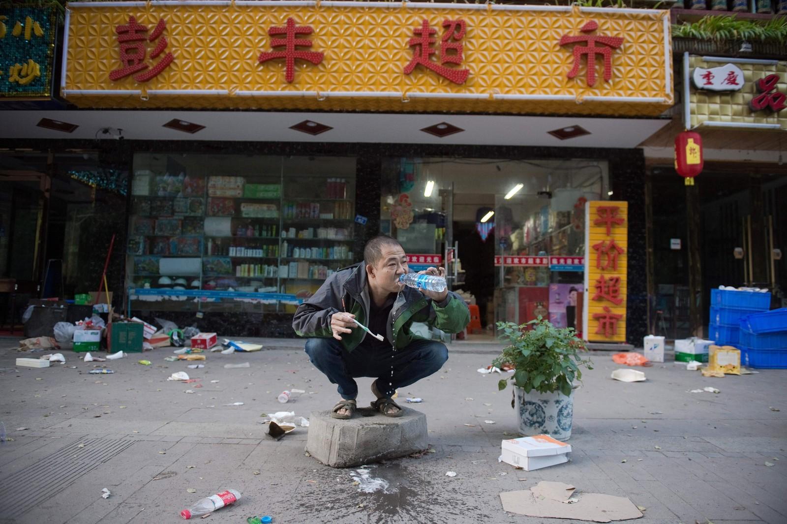 En mann pusser tennene på gaten utenfor butikken sin i Zhangzha etter jordskjelvet som tirsdag rammet Sichuan-provinsen i Kina. Jordskjelvet hadde en styrke på 6,5. Minst 19 er bekreftet døde og 250 skadd, men dødstallene er ventet å stige.