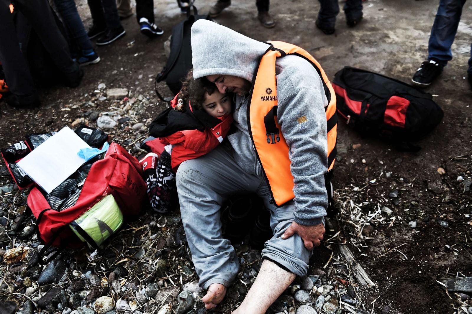 En mann klemmer en liten pike etter at de to har kommet i land på Lesvos 3. desember 2015.
