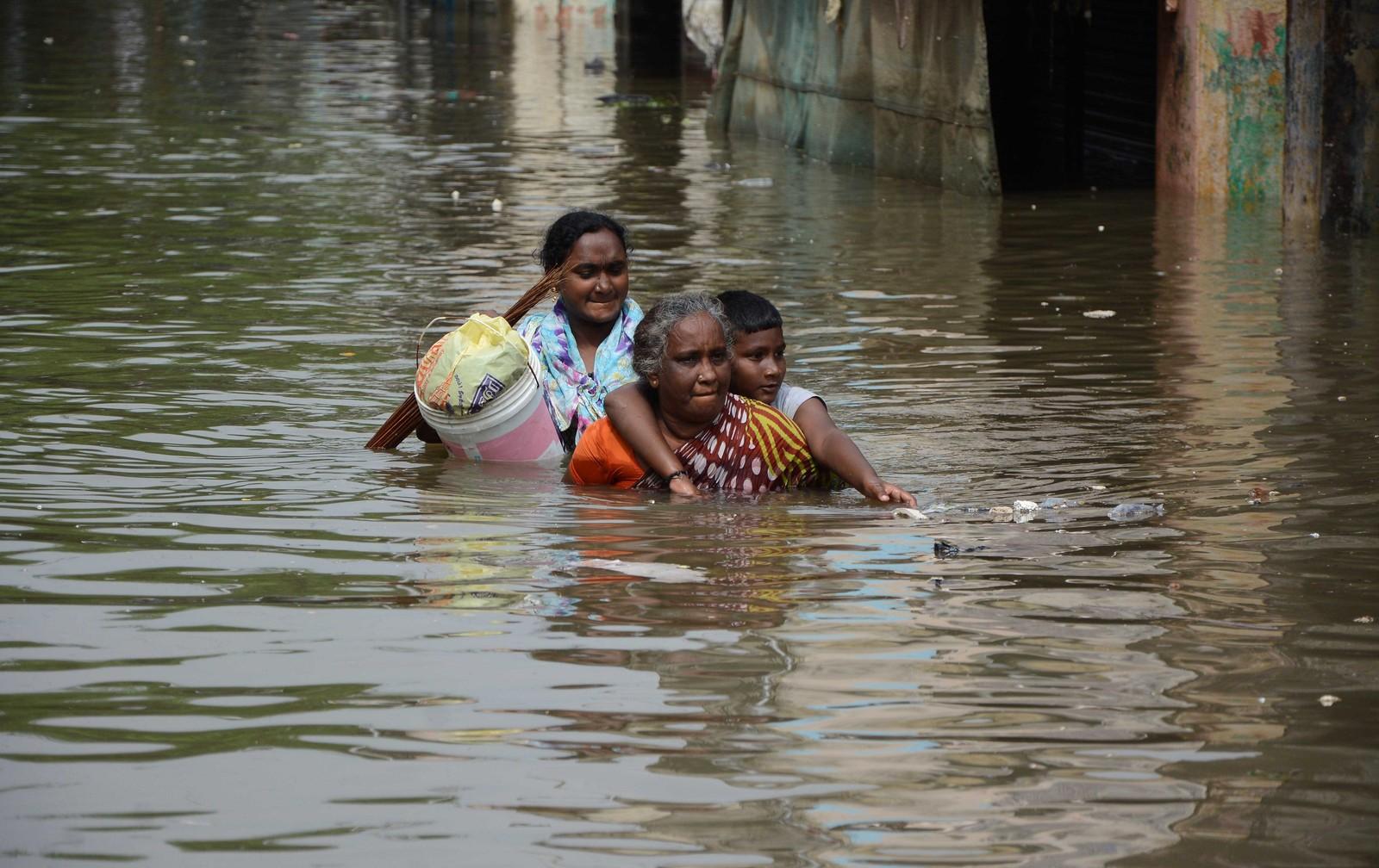 To kvinner og et barn evakuerer seg selv i Chennai. Dette er det kraftigste regnfallet på hundre år i delstaten Tamil Nadu i India.