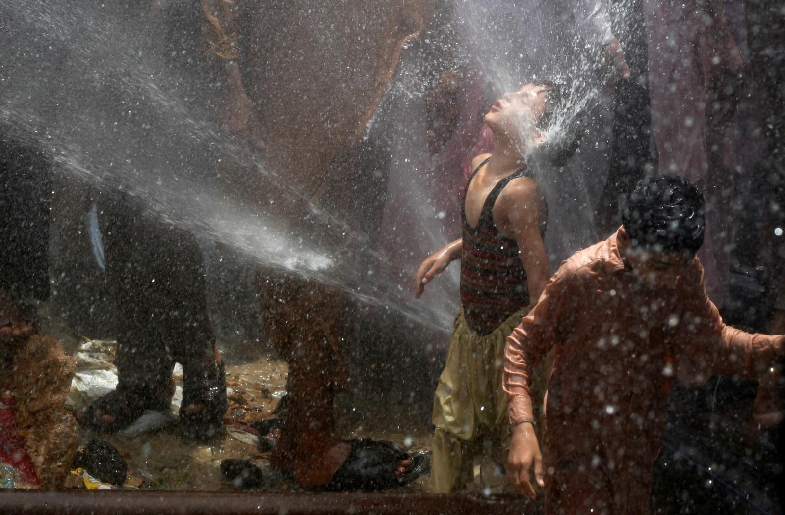 En gutt kjøler seg ned i varmen i Karachi. Demonstranter slo hull på vannledninger i protest mot strømbrudd i den pakistanske storbyen denne uka.