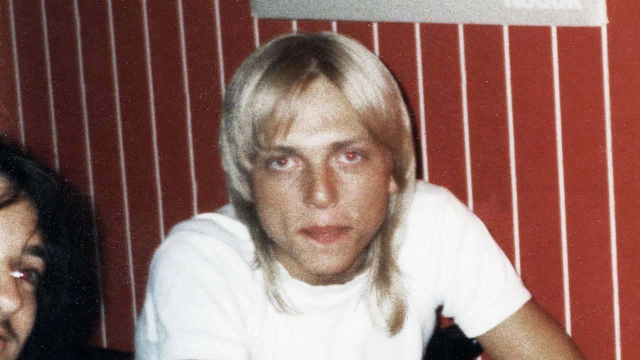Kjetil Manheim som tenåring foran en rød yttervegg, med halv-langt blondt hår.