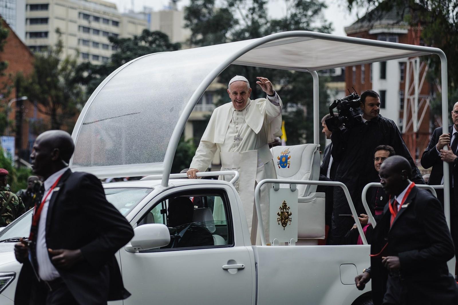 Paven besøker Nairobi i sin spesialbil, den såkalte Pope-mobile, som er bygd med store glassvinduer slik at folk skal se ham.