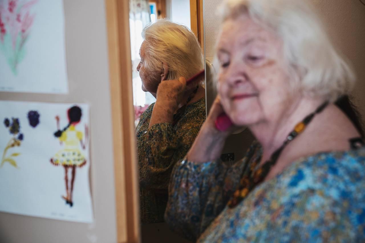 Anne Marie grer håret sitt mens hun ser seg i speilet. På veggen ved siden av henger noen tegninger hun har tegnet.