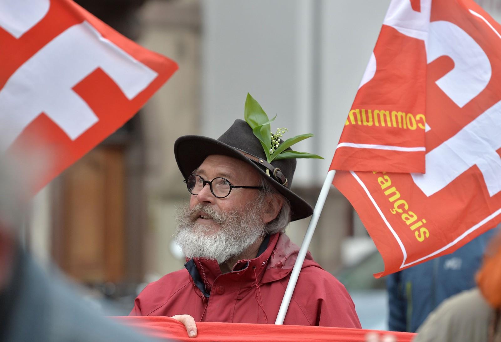 En mann i hatt med liljer markerer arbeidernes dag i Strasbourg, øst i Frankrike.