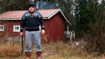 Mann med strikkegenser og grå joggebukse, øks i hånda