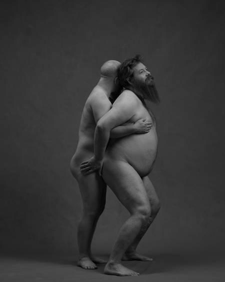 En naken mann står bak en annen naken mann med skjegg mens de holder rundt hverandre.