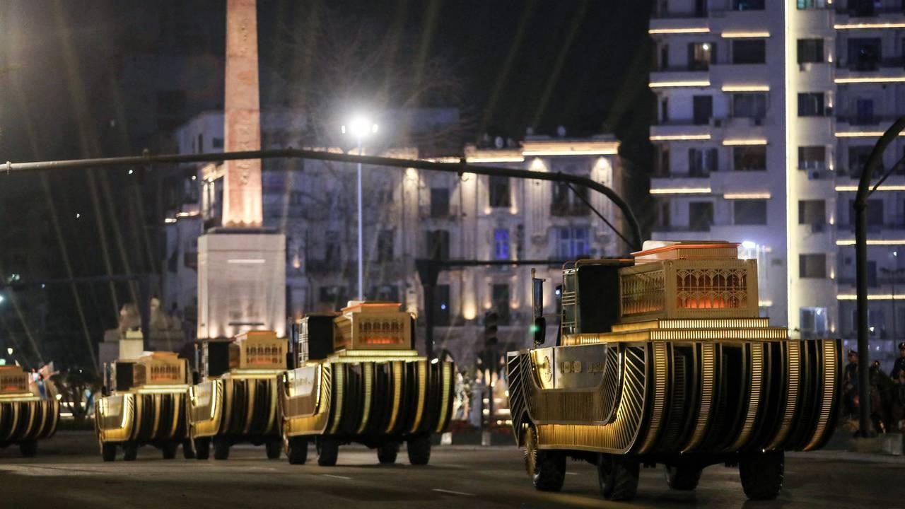 Mumiene fraktes på spesialbygde vogner til sitt nye hvilested. I bakgrunnen ses Ramses II's obelisk på Tahrirplassen i Kairo.