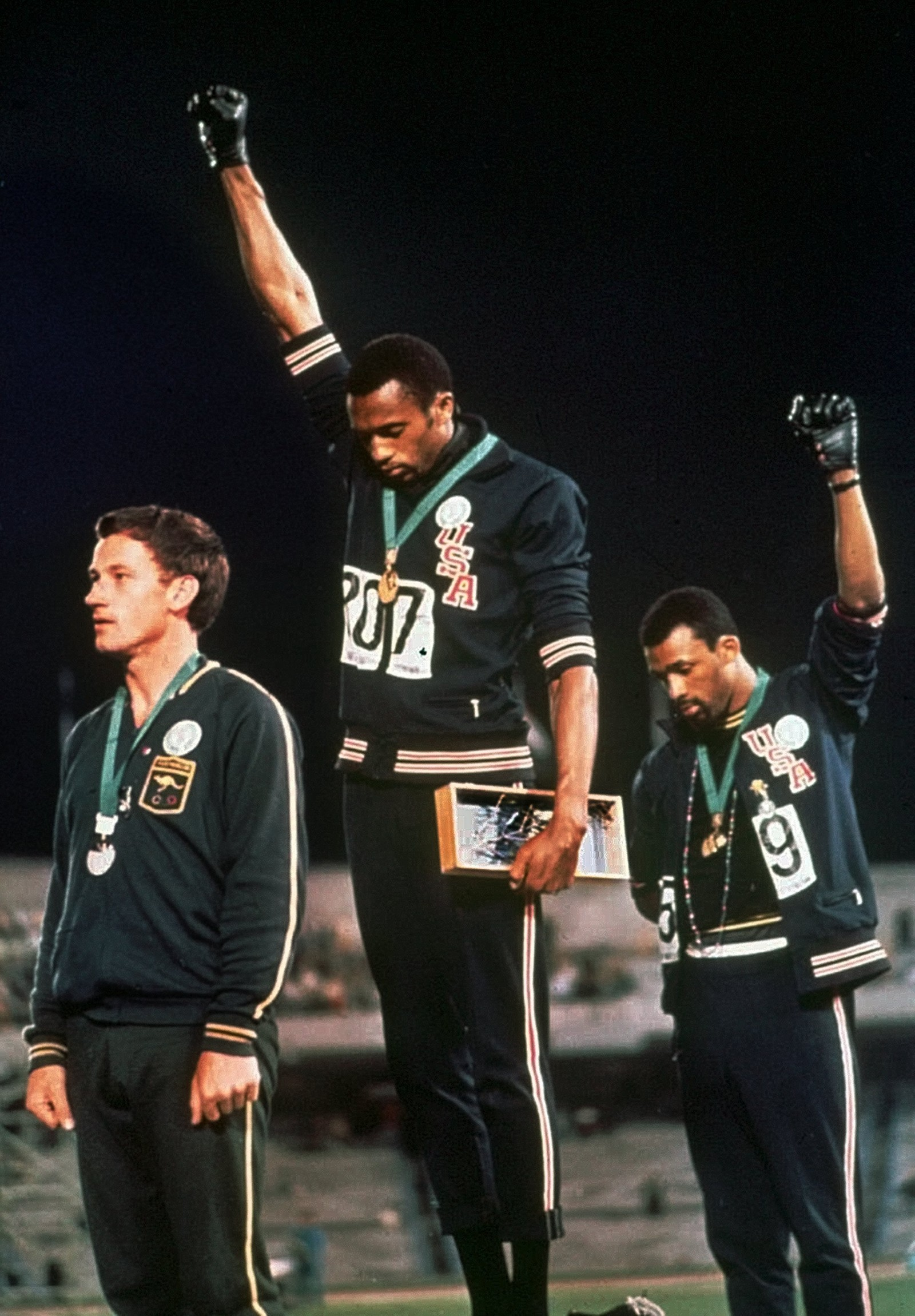 BLACK POWER: Tommie Smith, midten, og John Carlos fra USA. Australske Peter Norman til venstre under sommer-OL i Mexico 1968. Med sorte hansker løftet de nevene i verden som en protest mot diskriminering i USA.