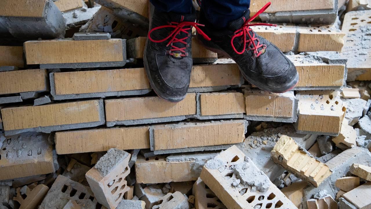 To føtter med vernesko står oppå en haug med murstein,