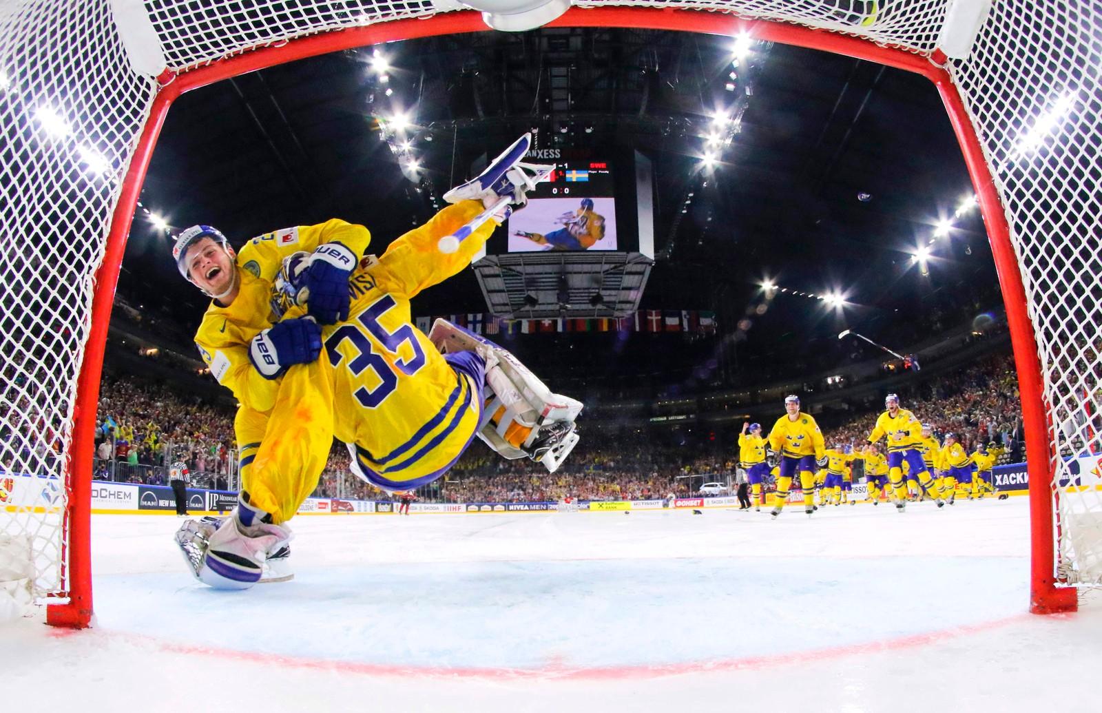 Det er ikke helt ufarlig å være keeperhelt. William Nylander takler Henrik Lundquist etter at han reddet alle forsøkene til motstander Canada i straffekonkurransen i VM-finalen i Köln i Tyskland. Sverige vant VM for tiende gang.