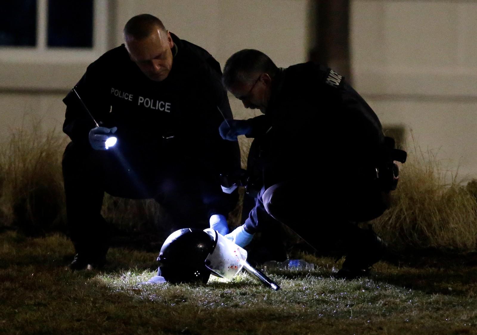 Politiet undersøker en hjelm på åstedet hvor en av politimennene ble skutt i Ferguson. AP Photo/Jeff Roberson)