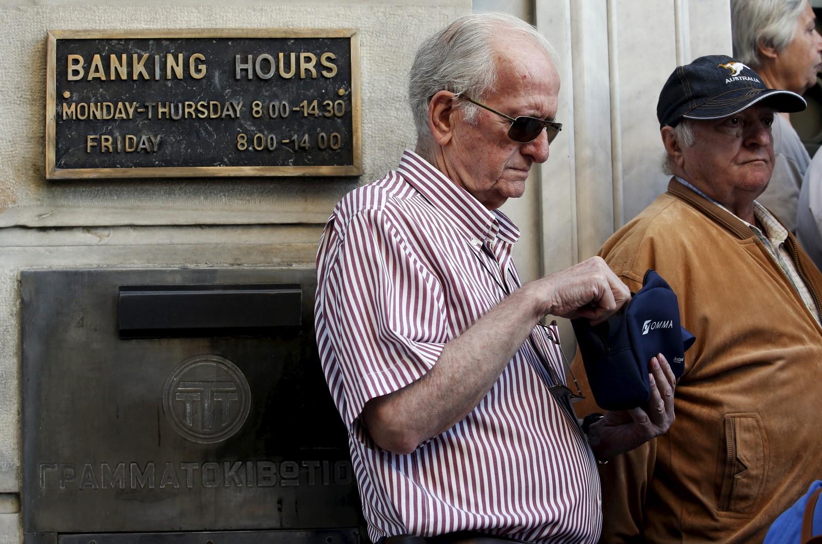 En pensjonist kikker i lommeboka si mens han venter i kø utenfor en bank i Aten.