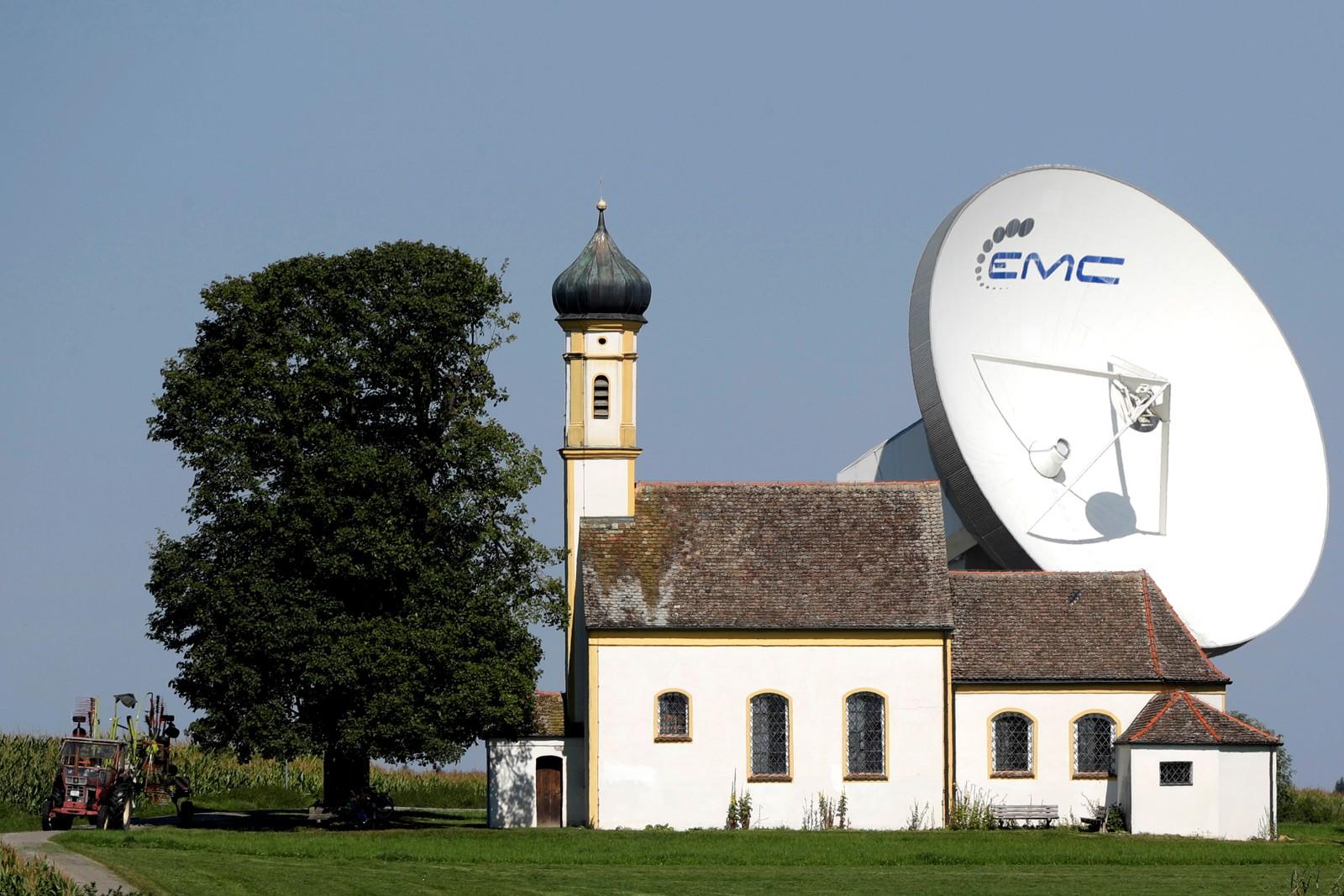 To landemerker i Raisting i Tyskland. Radioteleskopet er fra 1964. Kirken, St. Johannes der Täufer, var trolig ferdigbygget i 1428. Bildet er tatt 8. august.