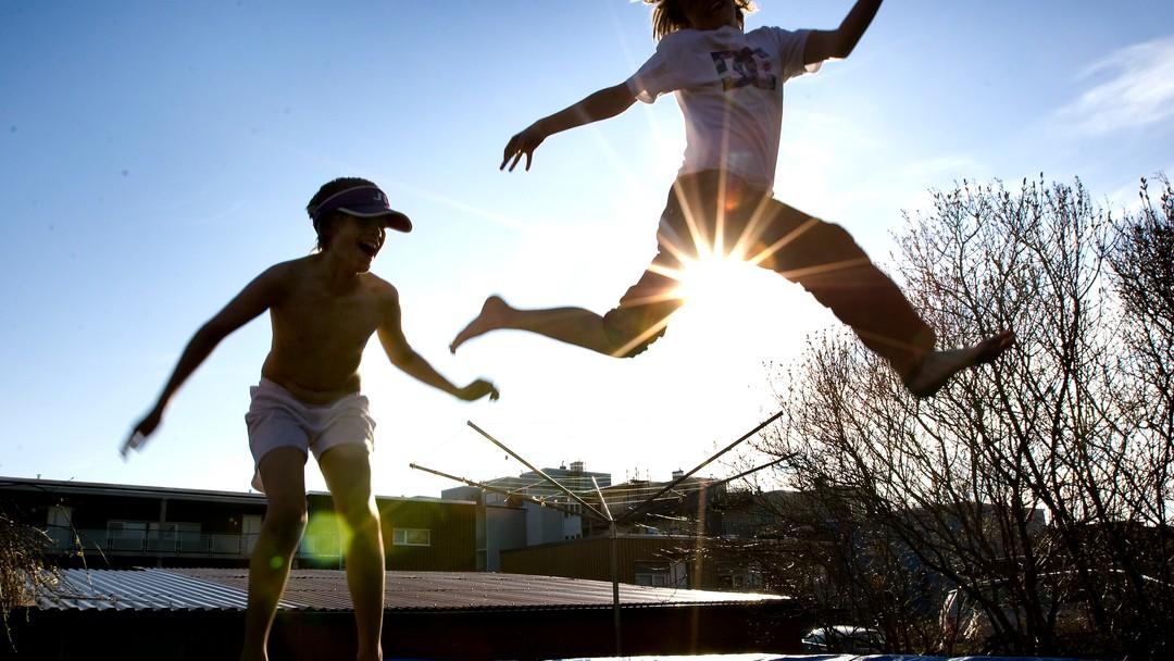 Gutter nyter våren og solen på trampoline i hagen. Barndom. Hopper. Sol. Livsglede. Lykke. Lykkelig. Vennskap. Modellklarert
