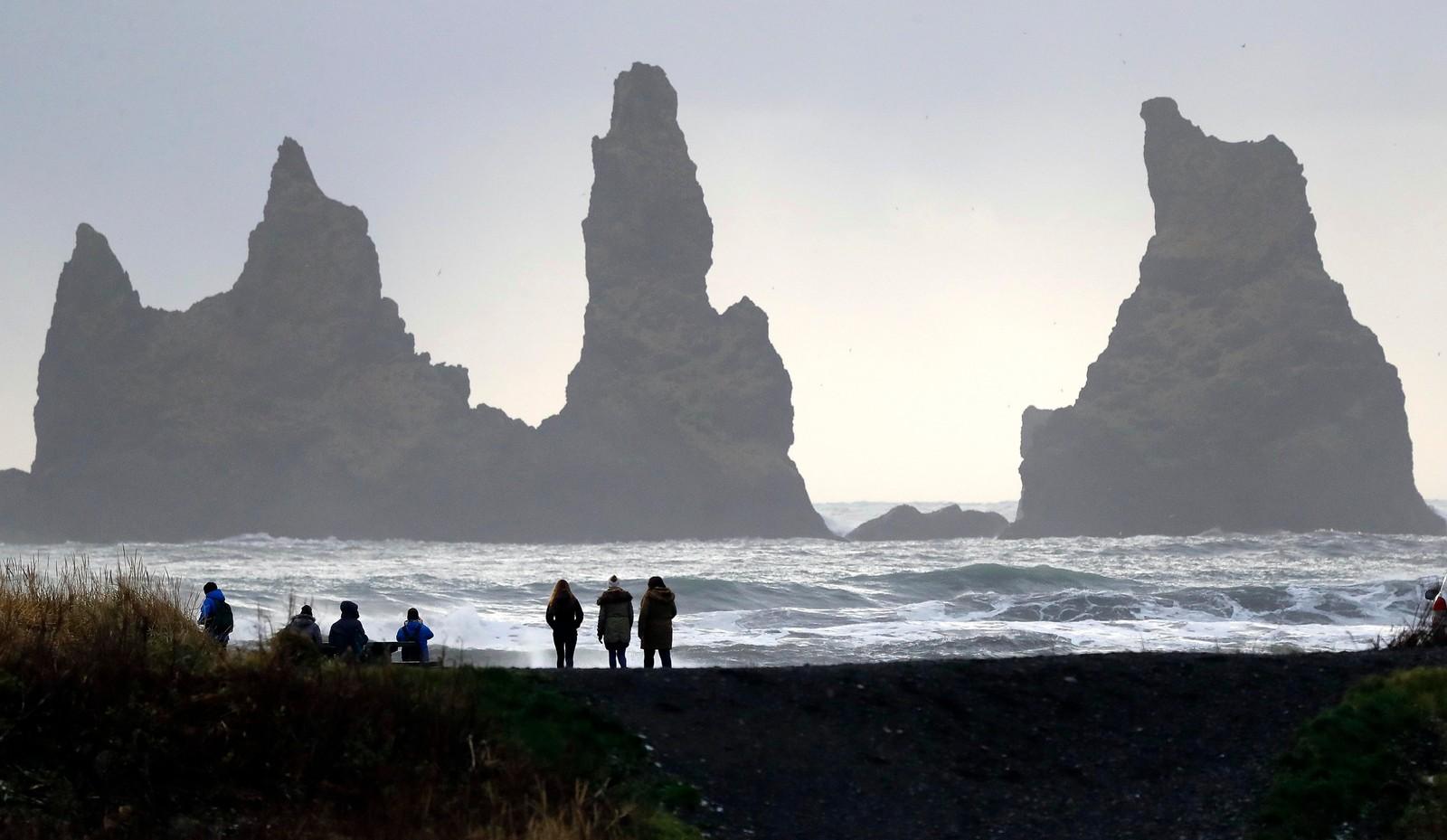 Den svarte stranden i Vik på Island med steinsøylene Reynisdrangar i bakgrunnen. Søylene består av svart basalt.