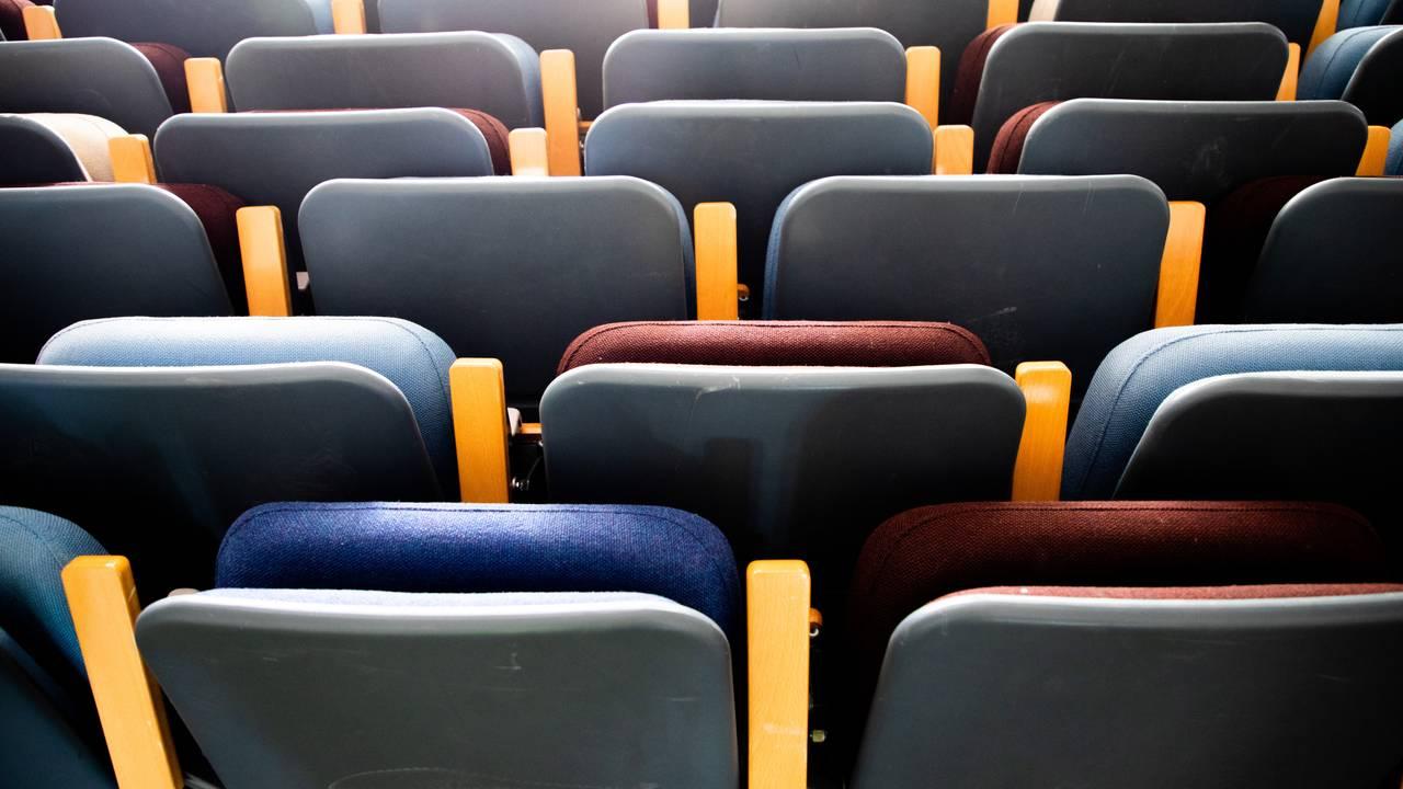 Sammenklappede seterader fra en gammel aula står stablet inntil hverandre på gulvet etter å ha blitt demontert. Setene er trukket i ullstoff i fargene blå, lilla og hvit.