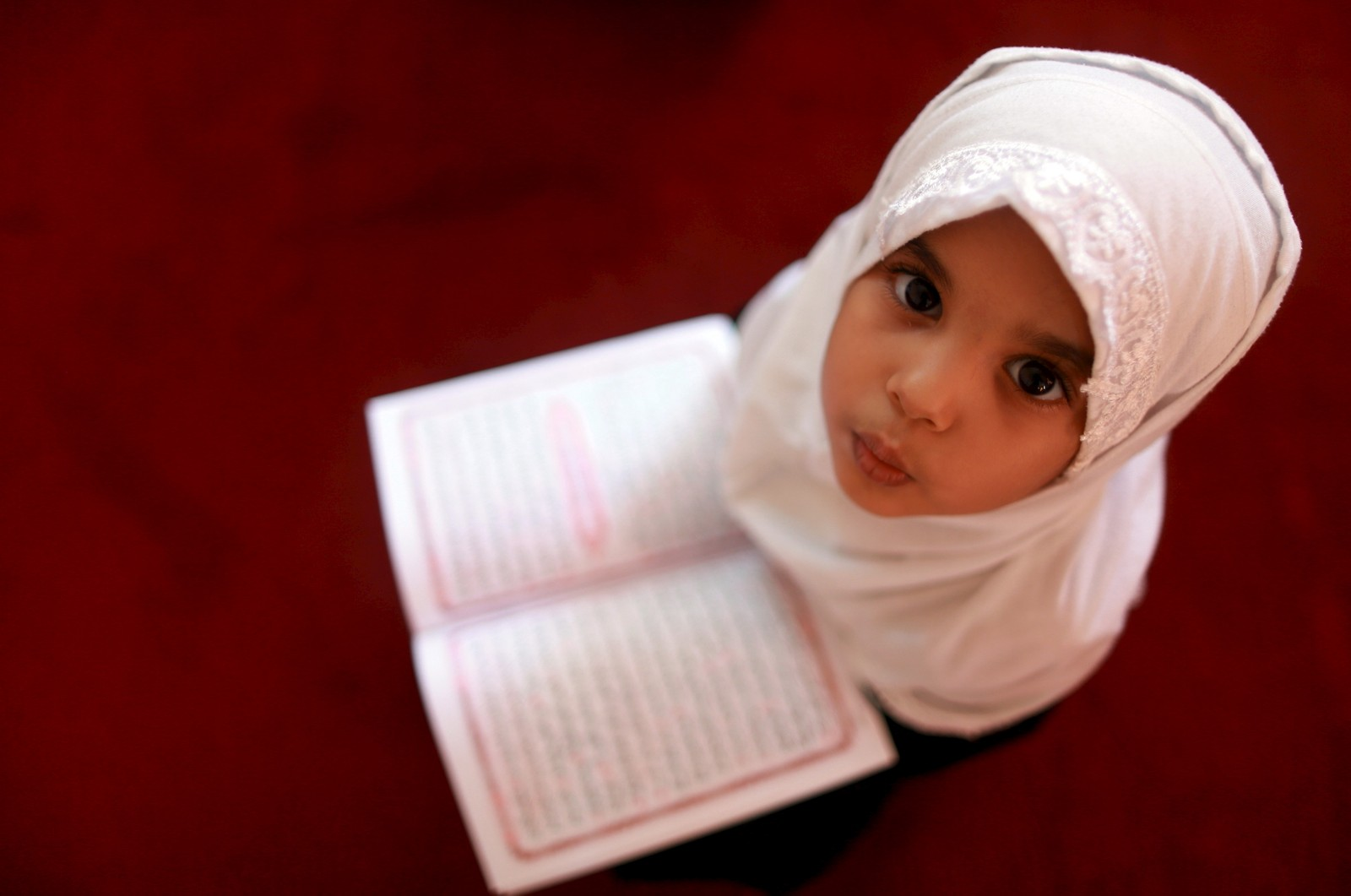 En liten jente leser Koranen på en koranskole under fastemåneden Ramadan i Benghazi, Libya.