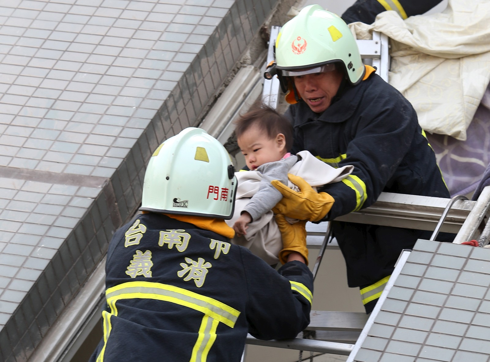 Redningsmannskap redder ut et lite barn fra ruinene av den 17 etasjer høye bygningen som har kollapset.