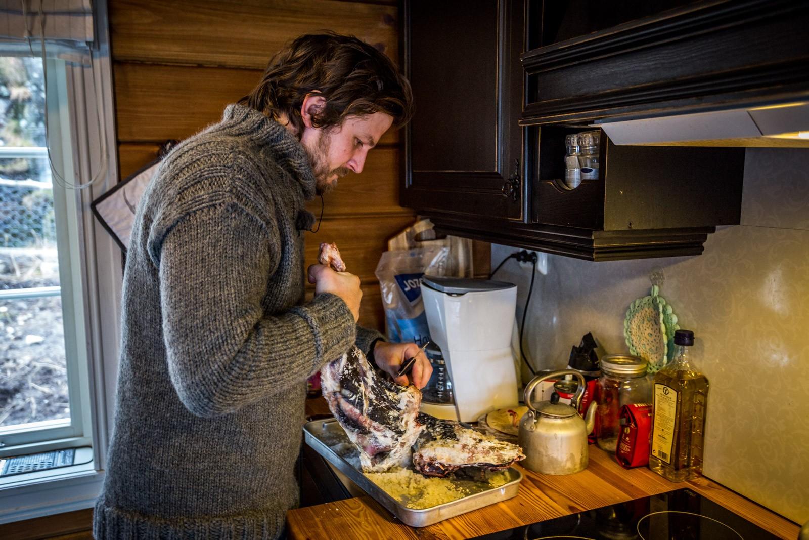 Severin brukar mykje tid på å lage god mat. Han prøver å vere mest mogleg sjølvforsynt på garden med kjøt og fisk. Her står han på kjøkkenet med eit fenalår.
