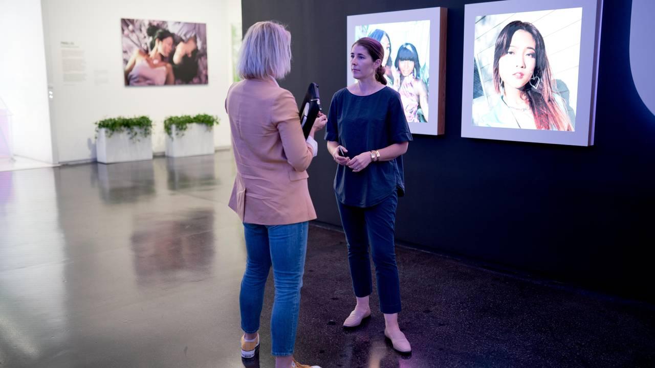 Journalist Annemarte Moland og Karina Newton er i Instagrams lokaler, og står foran noen skjermer som viser bilder av ulike personer.