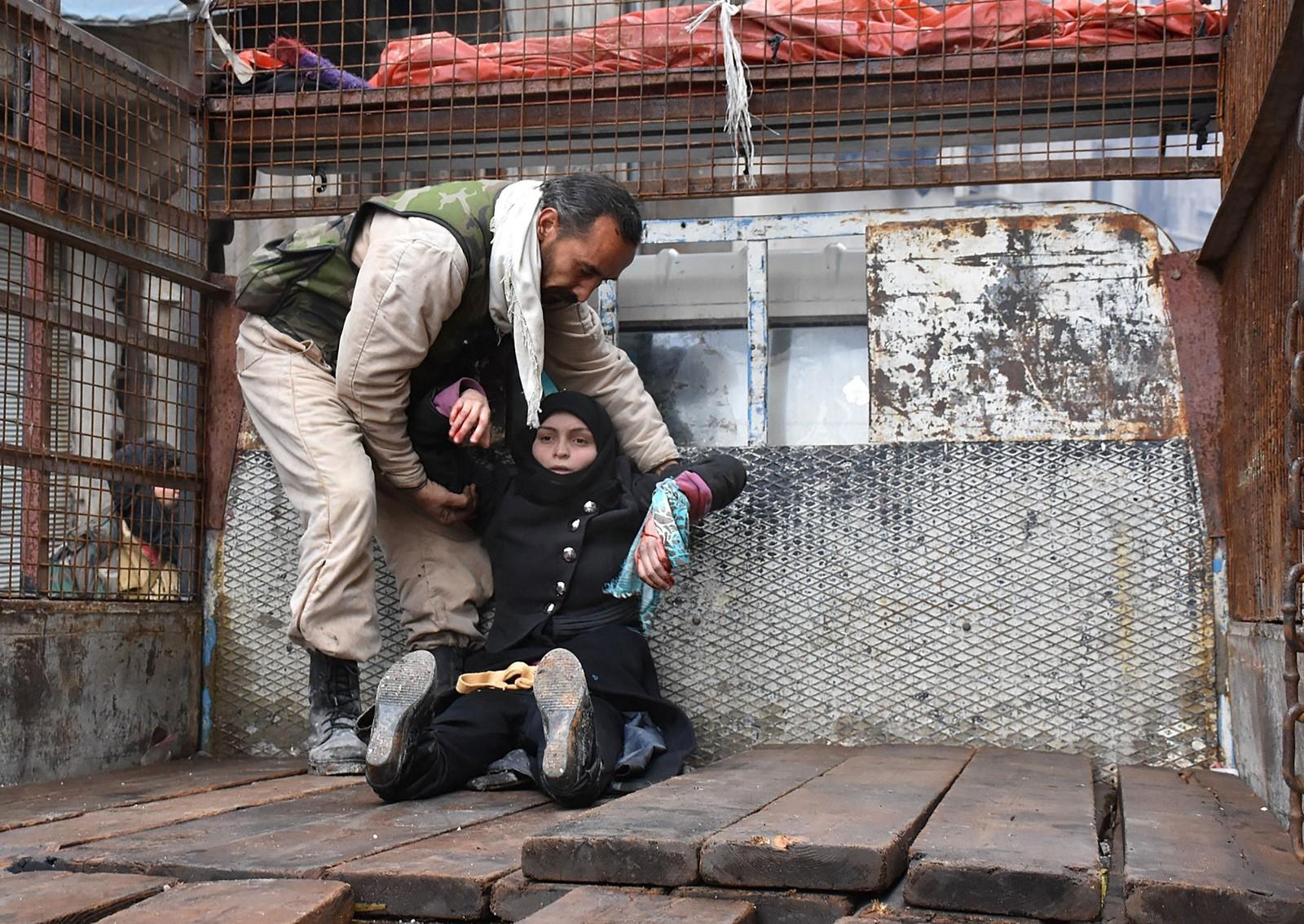 En skadet kvinne i al-Sukari i Aleppo blir hjulpet opp på et lasteplan under kamphandlingene.