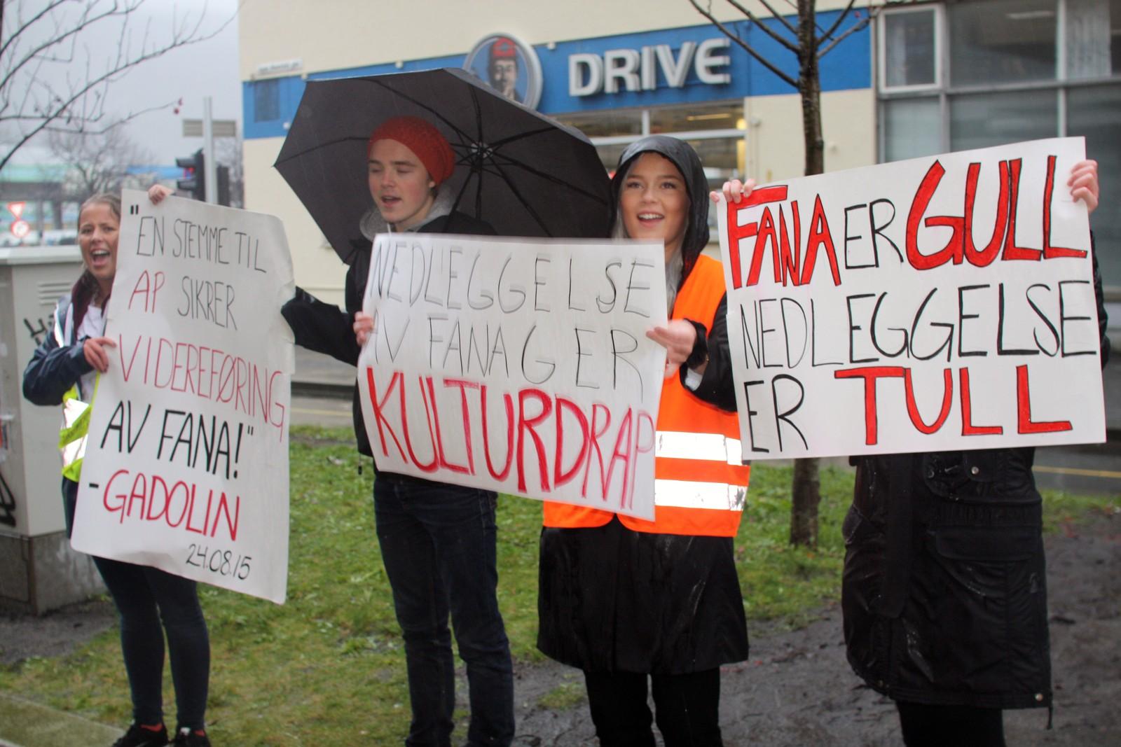 Elever fra Fana gymnas bærer bannere i protest mot nedleggelse av skolen.