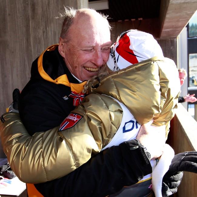 Therese Johaug i gulljakke får en god klem av kong Harald etter seier i Ski-VM 2011.