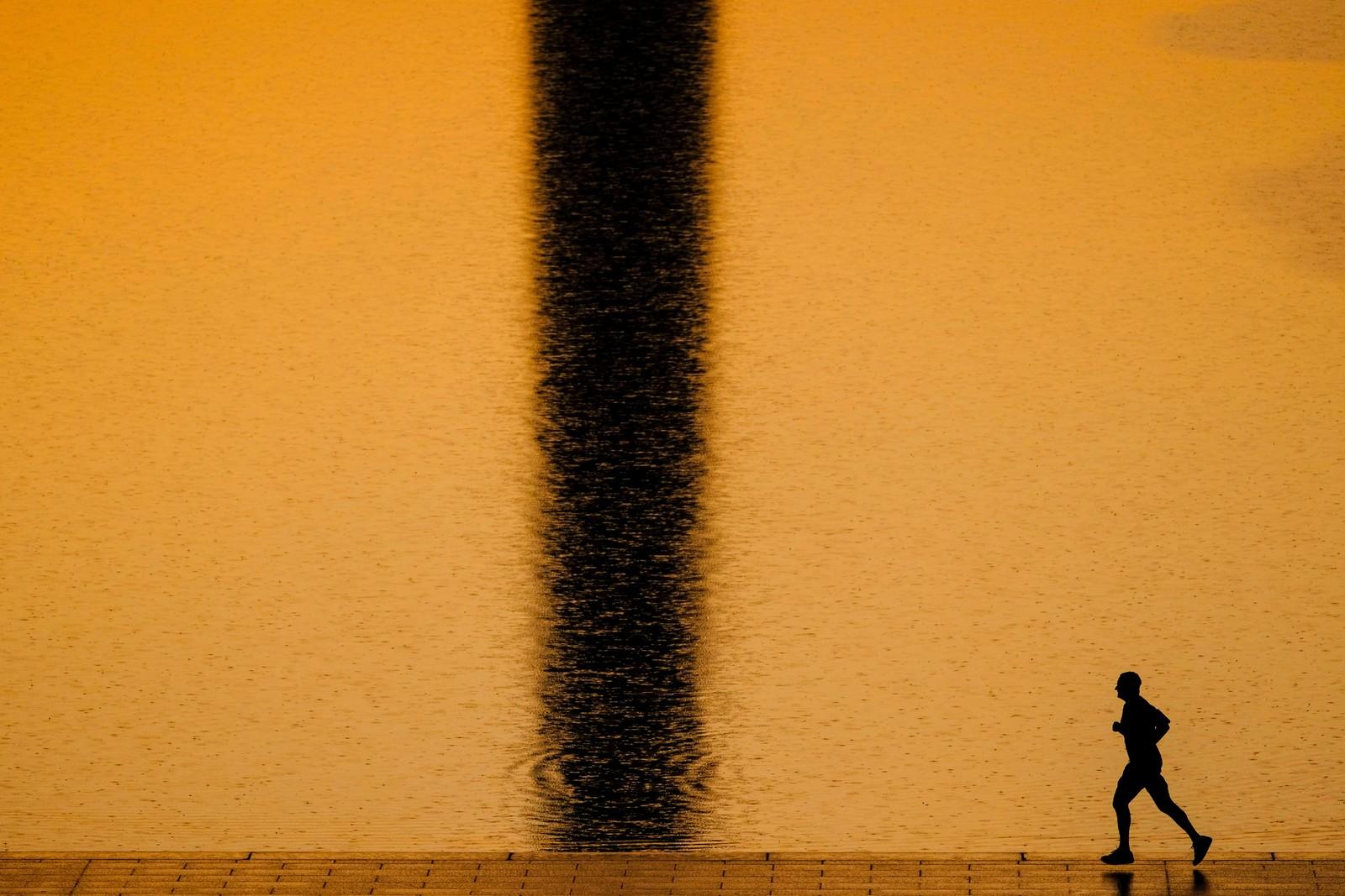 En morgenjogger løper forbi speilbildet til Washington-monumentet i bassenget som ligger i National Mall.