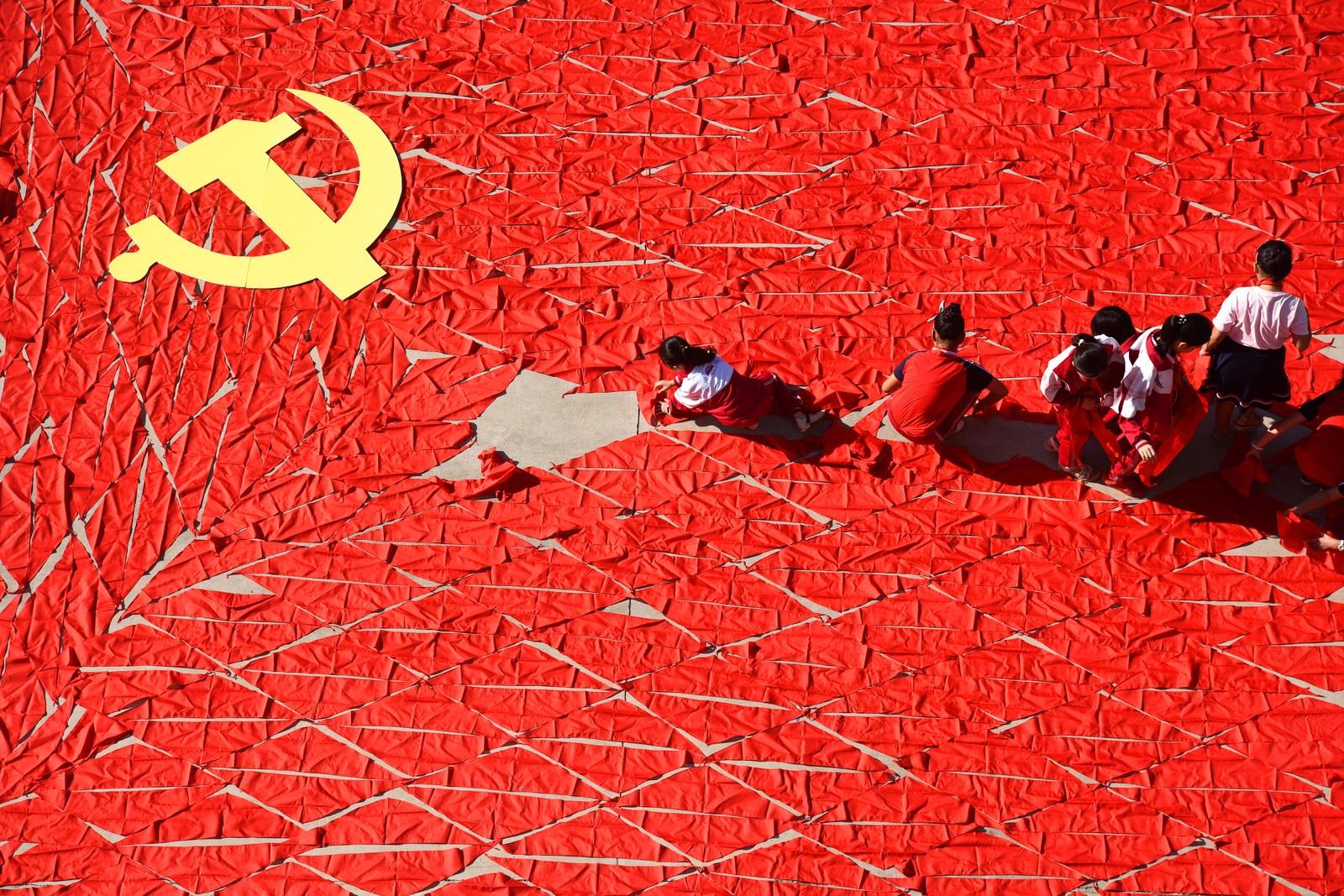 Elever på en barneskole i Linyi bruker skjerf til å lage det kinesiske flagget før det kommunistiske partiets 19. nasjonale kongress.