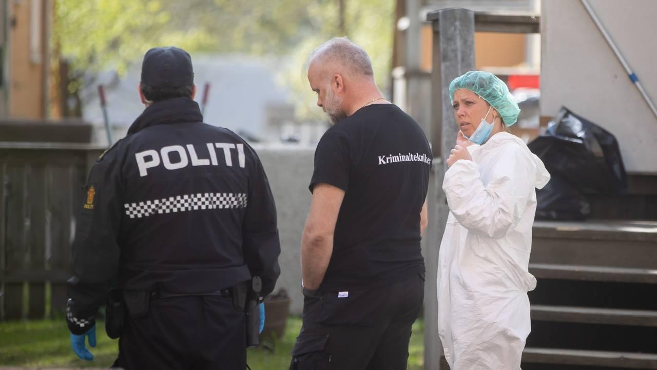 En uniformert politimann og to krimteknikere, en kledd i svart t-skjorte og ei kledd i hvit krimteknikerdrakt, utenfor det som er et drapsåsted på Lademoen i Trondheim.