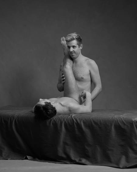 En naken mann ligger på rygg på senga med bene opp inntil brystet på en annen naken mann som står bak ham
