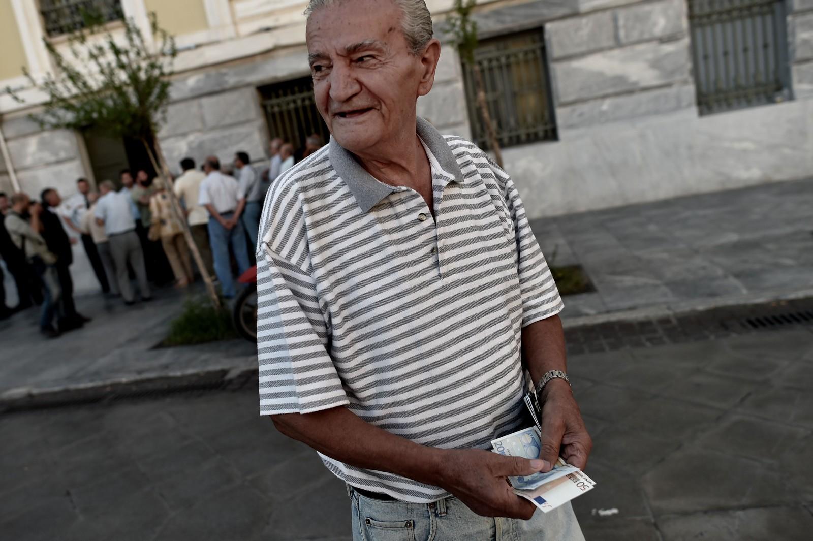 En gresk pensjonist utenfor banken etter at han fikk tatt ut penger.